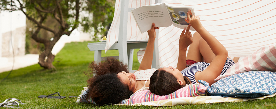 Two girls laying in the grass looking at a book together on a sunny day.